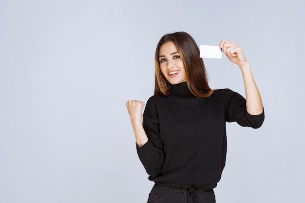 Kobieta pokazując swoją wizytówkę i wskazując na jej sukces pięścią.