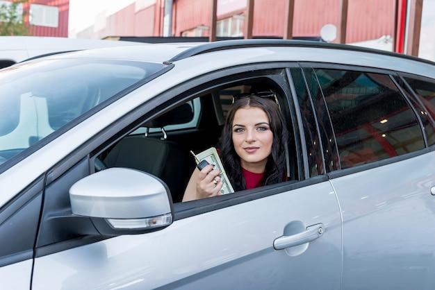 Kobieta pokazująca banknoty dolarowe z okna samochodu