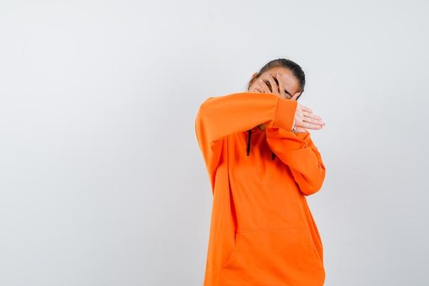 Kobieta pokazująca gest zatrzymania w pomarańczowej bluzie z kapturem i wyglądająca na zawstydzoną