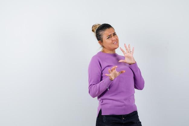Kobieta pokazująca gest zatrzymania w wełnianej bluzce i wyglądająca na zirytowaną