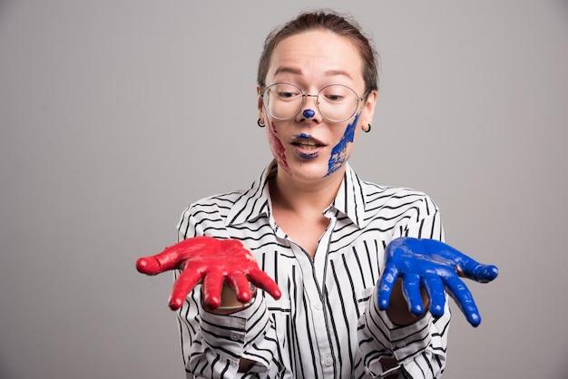 Kobieta pokazująca jej maluje ręce na szaro