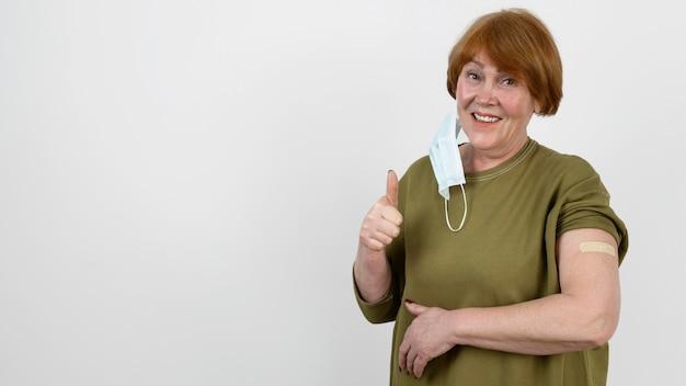 Kobieta pokazująca kciuk w górę i bandaż na ramieniu po szczepieniu