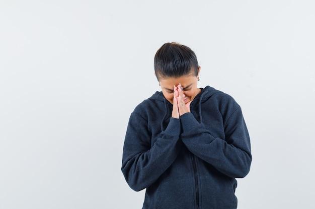 Kobieta pokazująca namaste gest w bluzie z kapturem i wyglądająca z nadzieją. przedni widok.