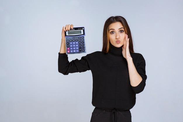 Kobieta pokazująca ostateczny wynik na kalkulatorze.