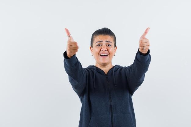 Kobieta pokazująca podwójne kciuki w górę w bluzie z kapturem i wyglądająca wesoło. przedni widok.