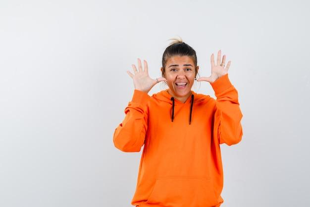 Kobieta pokazująca puste dłonie w pomarańczowej bluzie z kapturem i wyglądająca na wesołą