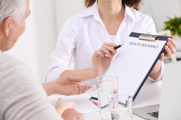 Kobieta pokazująca schowek i wskazująca na zalety ubezpieczenia zdrowotnego