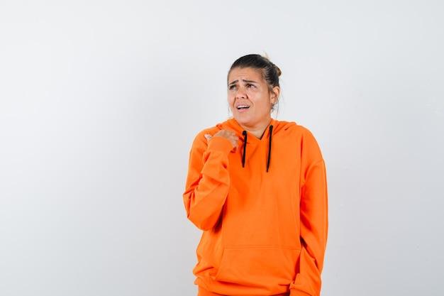 Kobieta pokazująca się, patrząc w pomarańczową bluzę z kapturem i wyglądając na zdezorientowaną