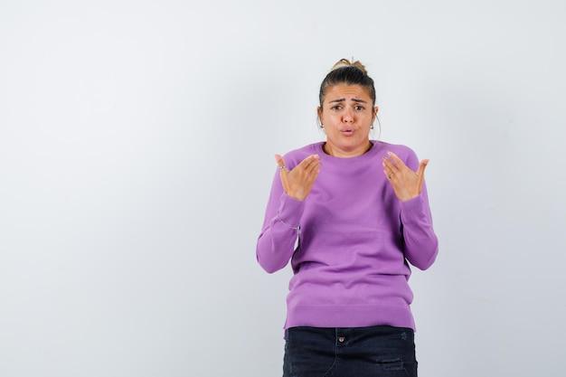 Kobieta pokazująca się w pytający sposób w wełnianej bluzce i wyglądająca na zdezorientowaną