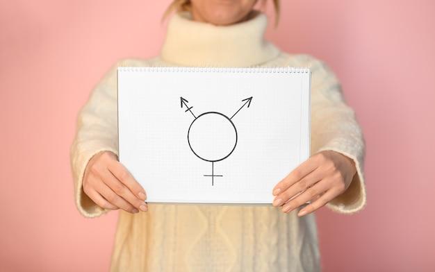 Kobieta pokazująca symbol osoby transpłciowej na kolorowej powierzchni, zbliżenie