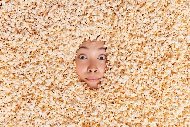 Kobieta pokazująca tylko twarz pokrytą pyszną słodką kukurydzą
