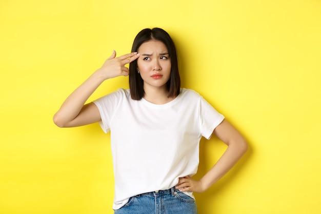 Kobieta pokazująca zabij mnie proszę gestem, strzelając sobie w głowę pistoletem palcowym z nudów, stojąc zdenerwowana na żółtym tle.
