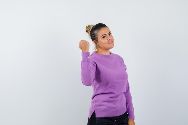 Kobieta pokazująca zaciśniętą pięść w wełnianej bluzce i wyglądająca na pewną siebie