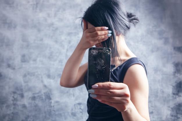 Kobieta pokazująca zepsuty telefon zakrywający twarz