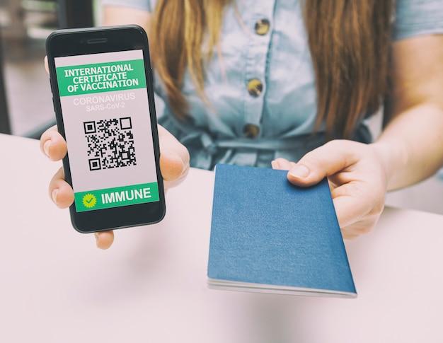 Kobieta pokazuje aplikację cyfrowego paszportu zdrowia w telefonie komórkowym i daje paszport