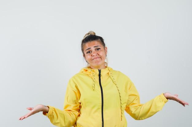 Kobieta pokazuje bezradny gest w sportowym garniturze i wygląda na zdezorientowanego. przedni widok.