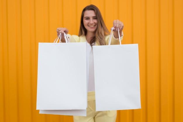 Kobieta pokazuje białe torby na zakupy