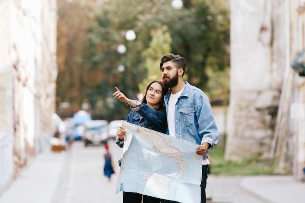 Kobieta pokazuje coś jej brodata mężczyzna pozycja wraz z turystyczną mapą