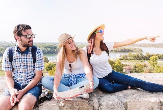 Kobieta pokazuje coś jej przyjaciele podczas wycieczkuje