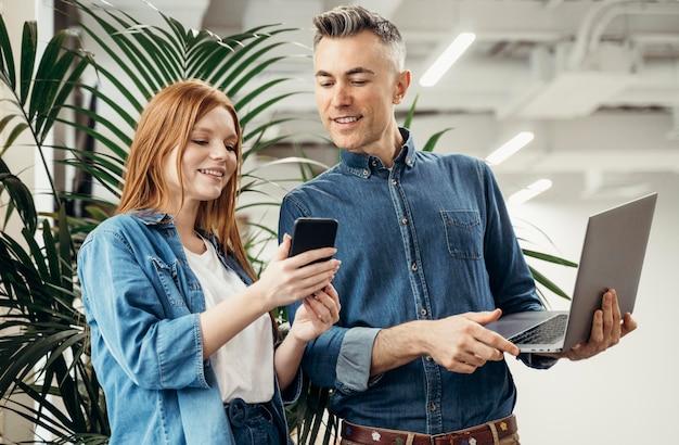 Kobieta pokazuje coś przez telefon współpracownikowi