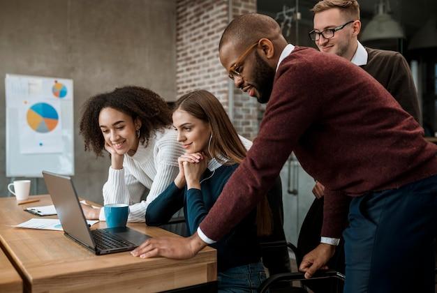 Kobieta pokazuje coś swoim współpracownikom podczas spotkania