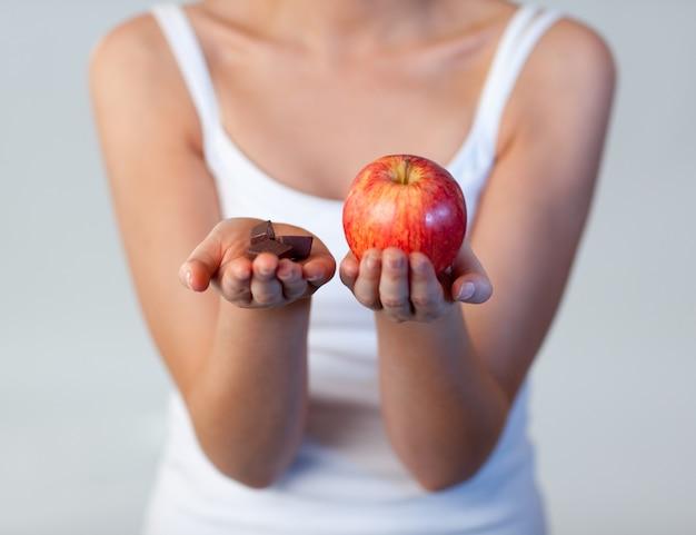 Kobieta pokazuje czekoladę i jabłko skupiamy się na czekoladzie