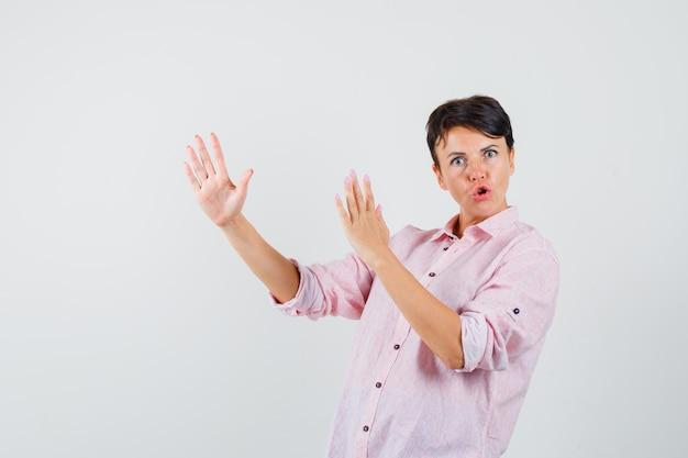 Kobieta pokazuje gest cios karate w różowej koszuli i wygląda potężnie. przedni widok.