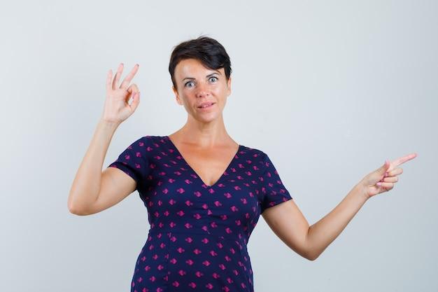 Kobieta pokazuje gest ok, wskazując na bok w sukience i wyglądająca na zdumioną