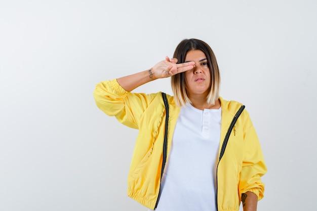 Kobieta pokazuje gest pistoletu na oko w koszulce, kurtce i wygląda pewnie. przedni widok.
