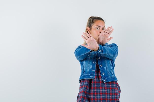 Kobieta pokazuje gest stopu w koszuli, kurtce i patrząc poważnie. przedni widok.