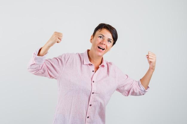Kobieta pokazuje gest zwycięzcy w różowej koszuli i wygląda szczęśliwy. przedni widok.