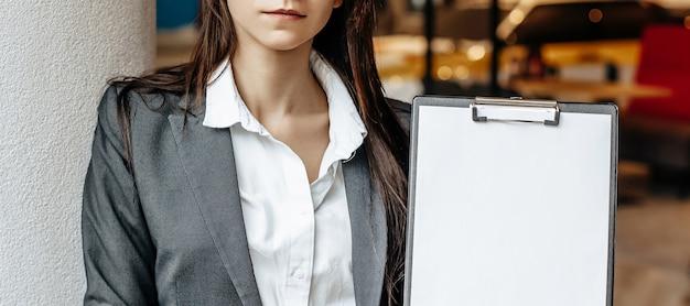Kobieta pokazuje informacje na tablecie. miejsce na reklamę. pomysł na biznes. dziewczyna trzyma dokumenty i wyjaśnia informacje. biała pusta kartka papieru.