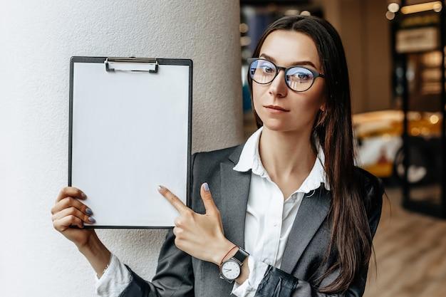Kobieta pokazuje informacje na tablecie.