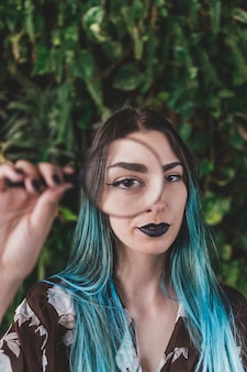 Kobieta pokazuje jeden oko przez powiększać - szkło