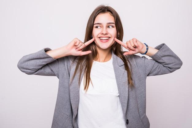 Kobieta pokazuje jej perfect prostych białych zęby na białym tle
