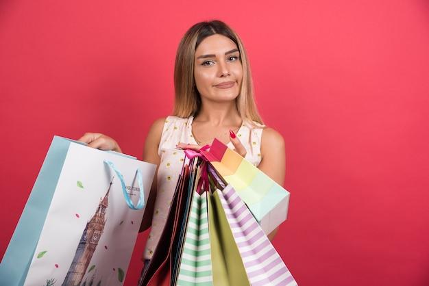 Kobieta pokazuje jej torby na zakupy na czerwonej ścianie.