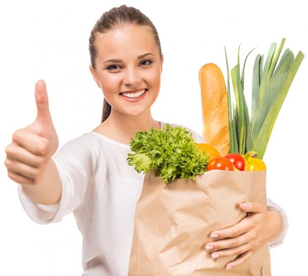 Kobieta pokazuje kciuk up i trzyma torba na zakupy.