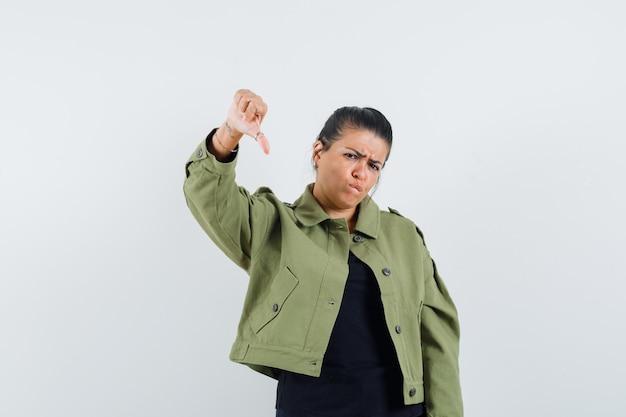 Kobieta pokazuje kciuk w dół w kurtce, koszulce i szuka niezadowolenia.