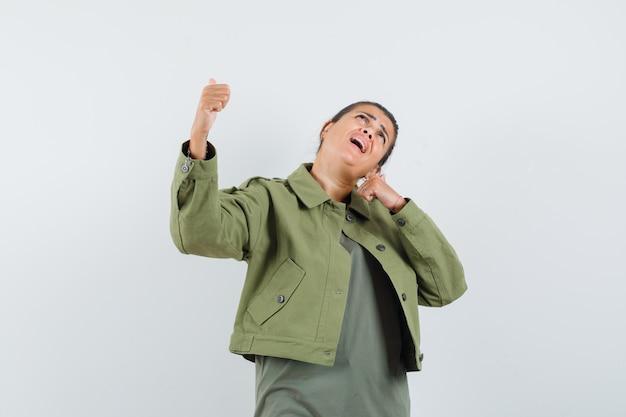 Kobieta pokazuje kciuki do góry w kurtce, t-shirt i szuka szczęścia.