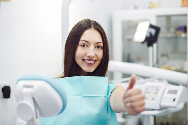 Kobieta pokazuje kciuki do góry w recepcji u dentysty