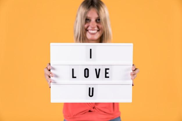 Kobieta pokazuje kocham cię tekst na lekkim pudełku