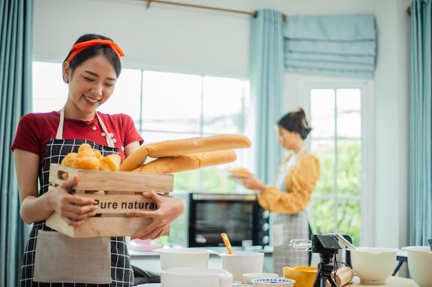 Kobieta pokazuje koleżance chleb, który upiekła.