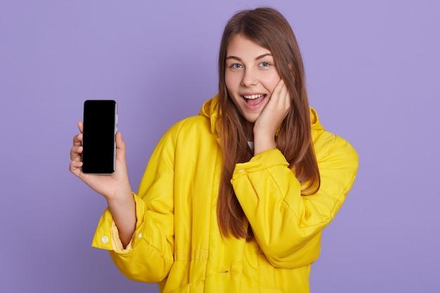 Kobieta pokazuje komuś ekran telefonu, wygląda na podekscytowaną, uśmiecha się szczęśliwie, mając na sobie żółtą koszulę, pozuje odizolowany na liliowej ścianie.