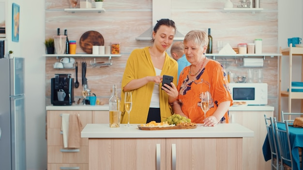 Kobieta pokazuje mamie zabawny film na smartfonie, siedząc w nowoczesnej kuchni przy stole, popijając kieliszek białego wina. osoba starsza ucząca się przeglądania za pomocą technologii internetowej