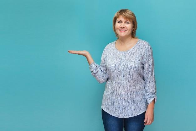 Kobieta pokazuje miejsce na reklamę. kobieta w średnim wieku w bluzce na niebiesko-zielonym tle