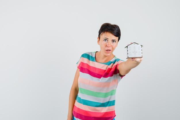 Kobieta pokazuje model domu w t-shirt w paski i wygląda na zaniepokojoną