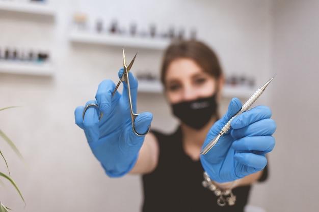 Kobieta pokazuje narzędzia do manicure.
