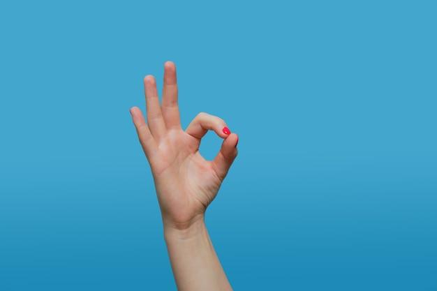 Kobieta pokazuje ok gest. kobieta ręka z czerwonym manicure żelowym na niebieskiej ścianie kopiowanie miejsca