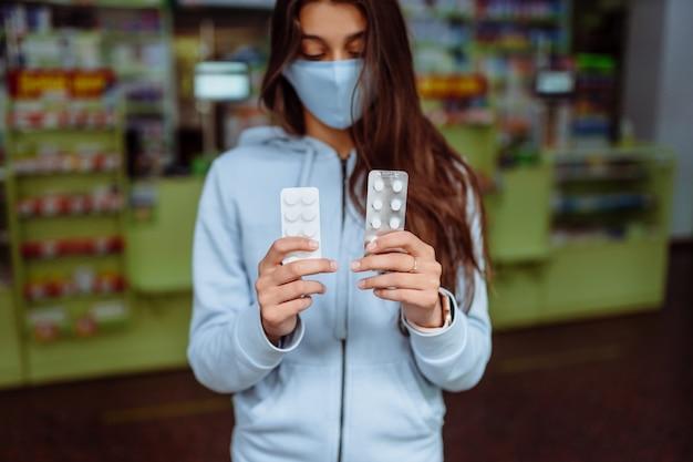 Kobieta pokazuje pigułki, witaminy lub pigułki w ręku. covid19.