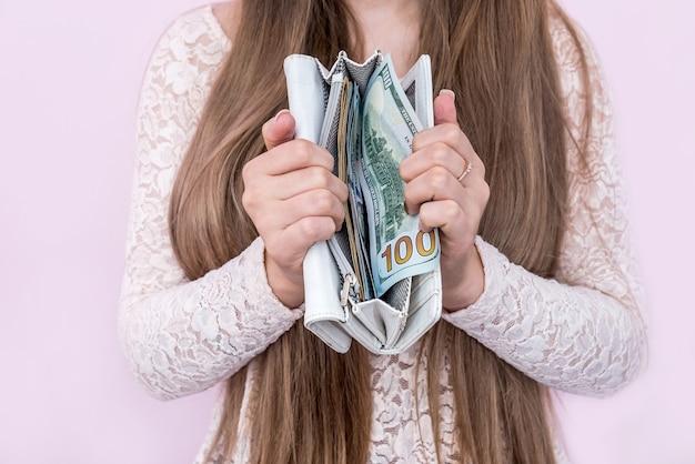 Kobieta pokazuje portfel z banknotami dolara w środku
